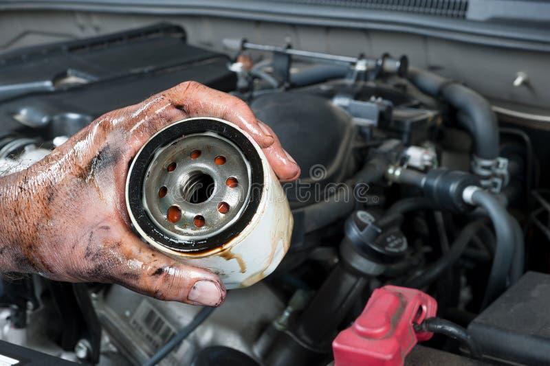 拿着油滤清器的汽车机械师 库存照片
