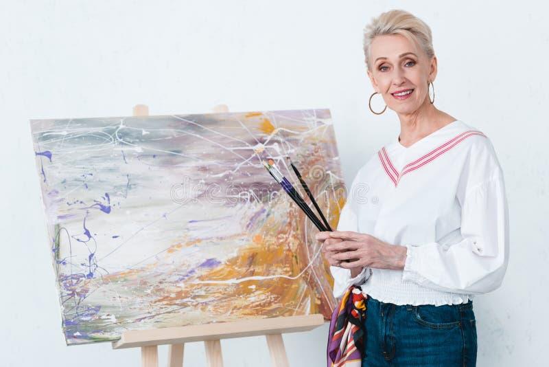 拿着油漆刷和站立在画架的绘画附近的资深典雅的女性艺术家 免版税库存照片