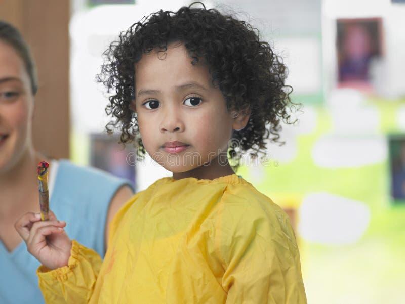 拿着油漆刷的逗人喜爱的女孩 免版税库存图片