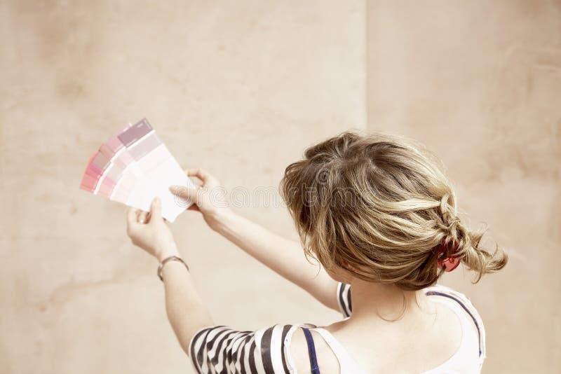 拿着油漆颜色样片的妇女 免版税库存图片