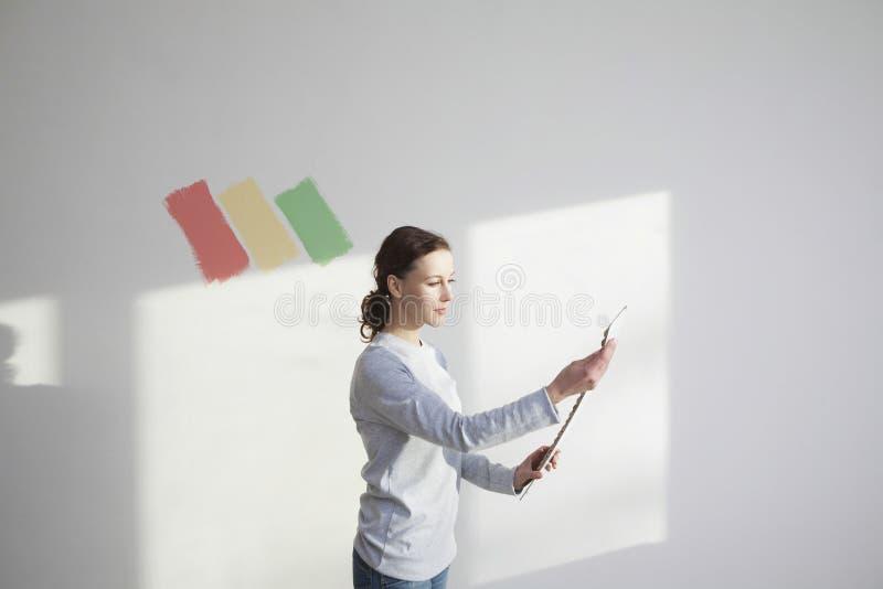 拿着油漆颜色样片的妇女 免版税库存照片