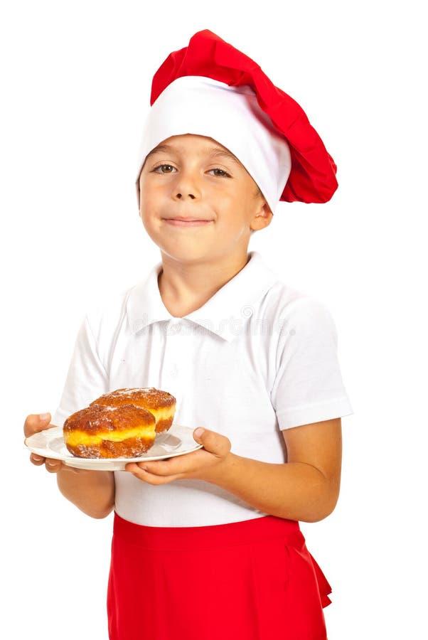 拿着油炸圈饼的愉快的厨师男孩 图库摄影