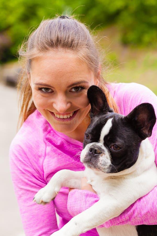 拿着法国牛头犬的微笑的妇女外面 库存照片