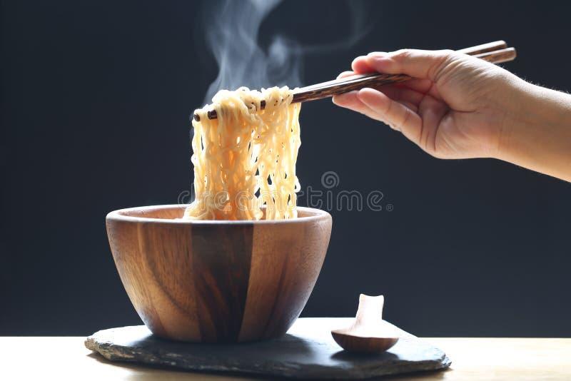 拿着泡面的筷子在杯子有烟上升的和大蒜的妇女手在黑暗的背景,高危险钠的饮食 免版税库存图片