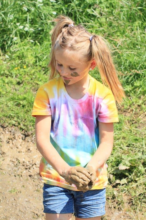 拿着泥的讨厌的女孩 免版税库存照片