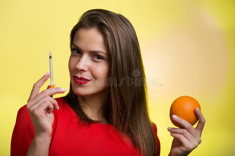 拿着注射器和桔子的妇女 图库摄影