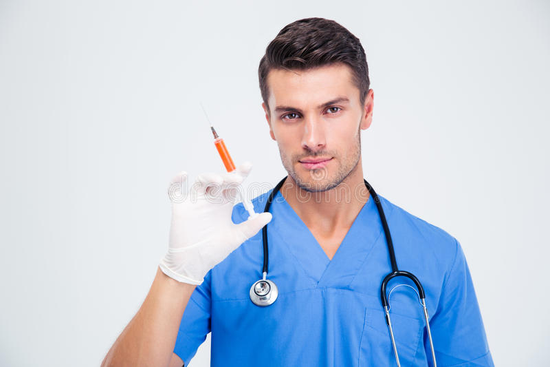 拿着注射器的一位英俊的男性医生的画象 库存照片