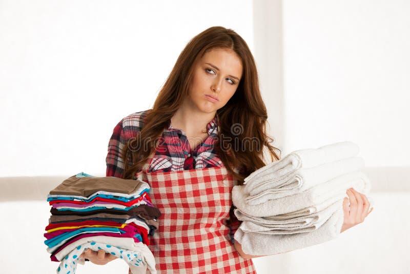 拿着洗衣店的美丽的少妇,在她完成了ironin后 库存图片