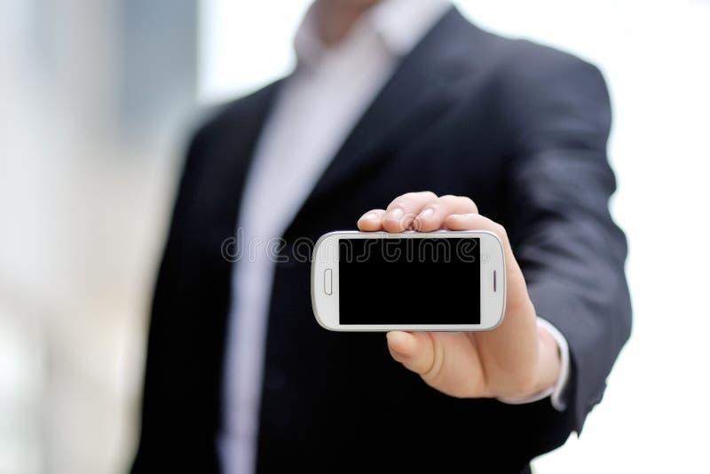 拿着流动巧妙的电话的商人手中 免版税库存图片