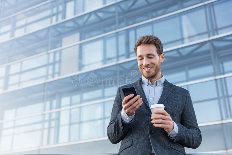 拿着流动手机的商人使用应用程序短信的sms消息佩带的衣服 使用智能手机的年轻都市专业人在 免版税库存照片
