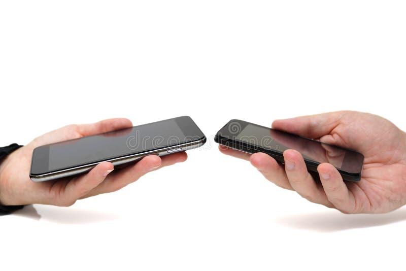 拿着流动智能手机的两只手,当转移数据为时 库存图片