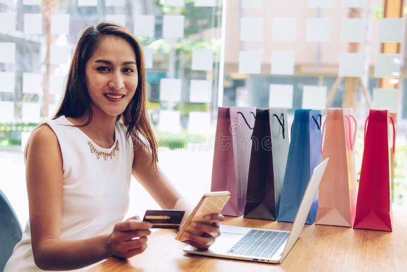 拿着流动智能手机&信用卡网上付款的妇女与购物带来在桌上 消费者至上主义生活方式概念 免版税库存照片