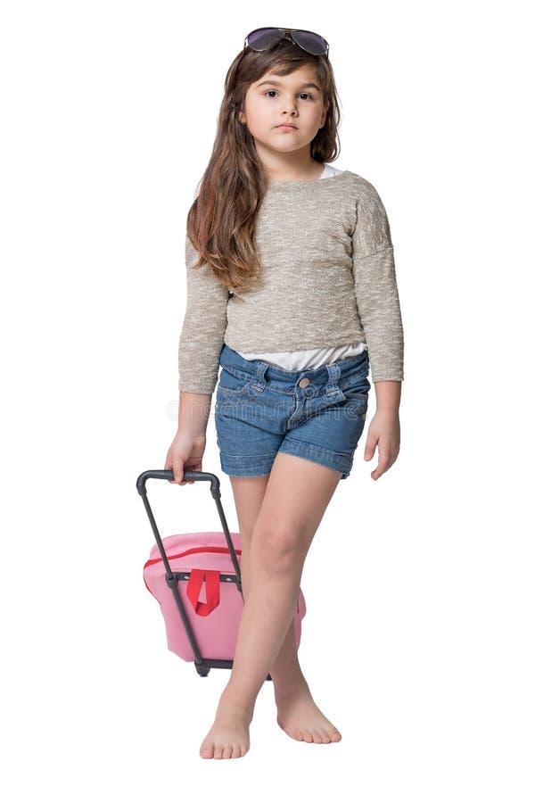 拿着浅粉红色手提箱的凉快的小女孩 库存图片