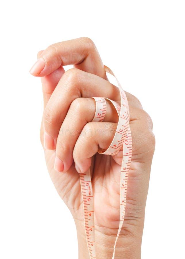 拿着测量的磁带的妇女手被隔绝在白色背景 免版税库存图片