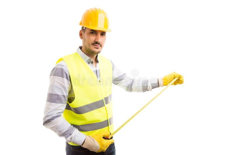 拿着测量的磁带米的确信的木匠或工程师 免版税库存图片