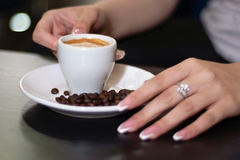 拿着浓咖啡在书桌上的女孩手咖啡杯在酒吧 库存照片