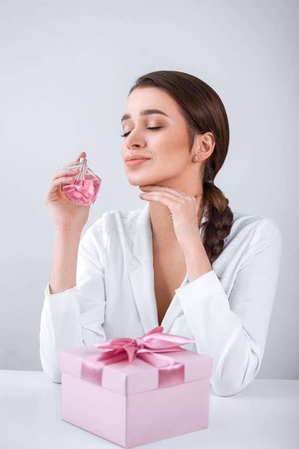 拿着浪花瓶香水和嗅到芳香,在桌上的一件礼物的年轻美丽的妇女 库存图片