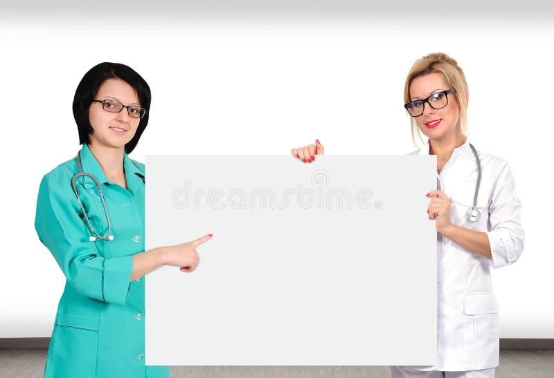 拿着海报的两医生 库存图片