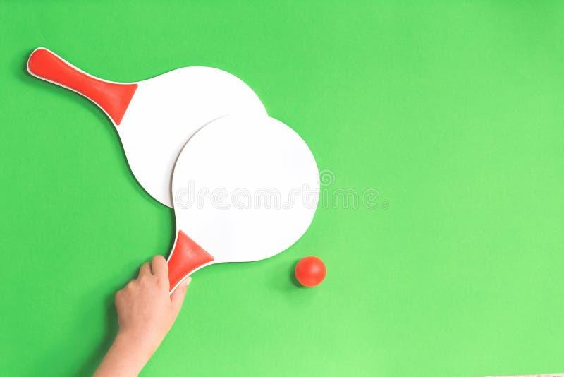 拿着海滩网球桨球拍的手 免版税图库摄影