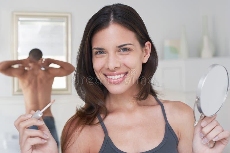 拿着涂药器和镜子的愉快的妇女 免版税库存图片
