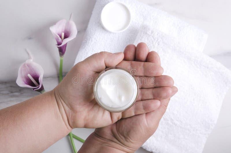 拿着润湿的奶油的妇女反对白色毛巾和花 秀丽做法的概念 免版税库存照片