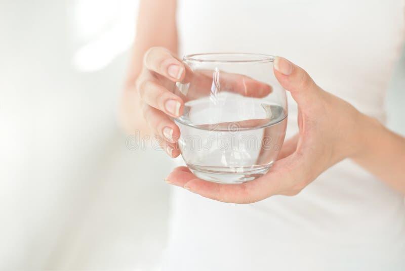 拿着清楚的杯水的女性手 一杯干净的矿泉水在手上,健康饮料 库存图片