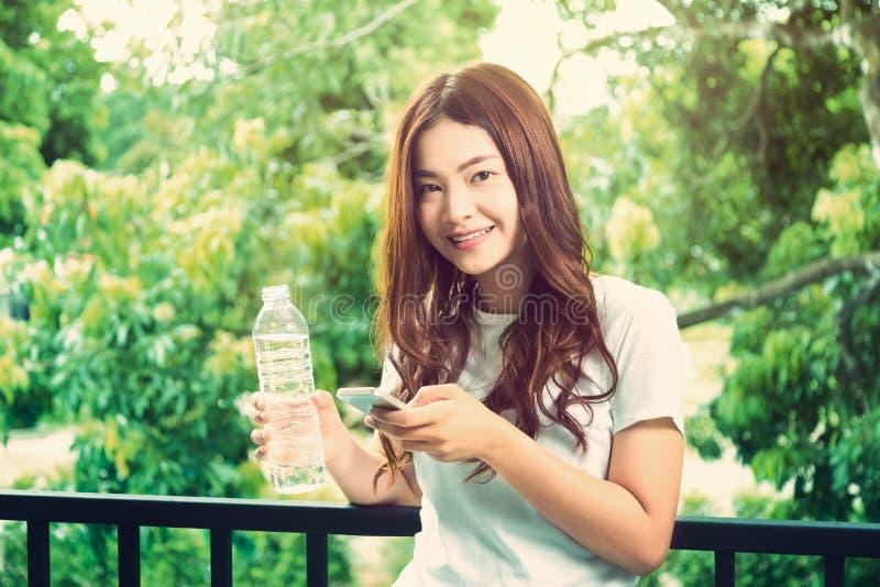 拿着清楚的瓶o的愉快的年轻美丽的健康亚裔妇女 库存照片