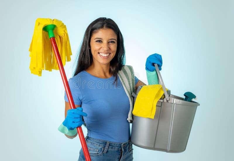 拿着清洁工具和产品在桶的年轻可爱的妇女隔绝在蓝色背景 免版税图库摄影