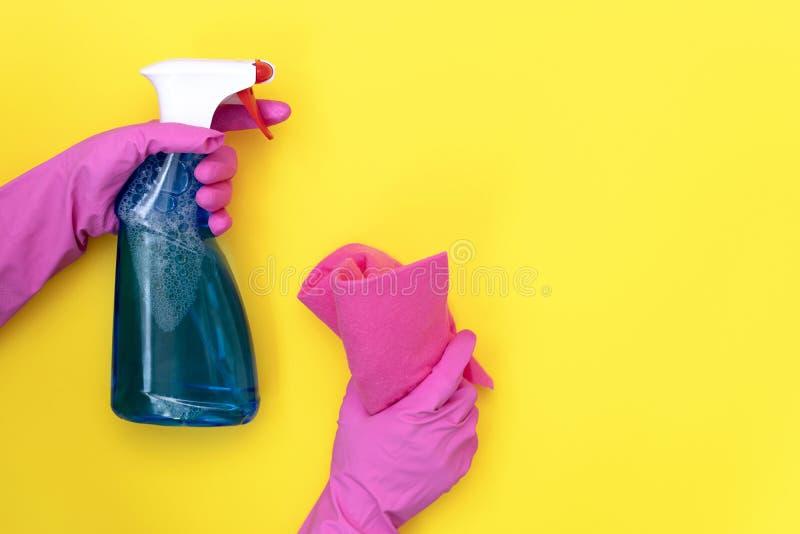 拿着清洁毛巾和洗涤剂浪花瓶在黄色背景的妇女 免版税图库摄影