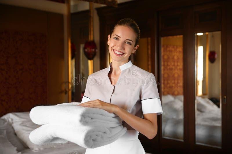 拿着清洁毛巾的女服务生在屋子里 库存图片