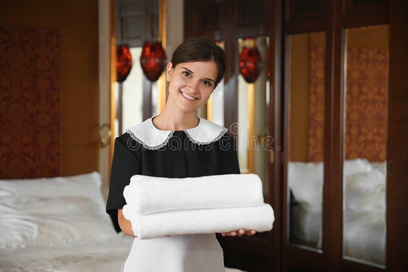 拿着清洁毛巾的女服务生 图库摄影