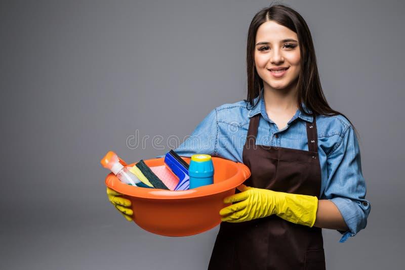 拿着清洁工具和产品在桶的少妇,隔绝在灰色 库存照片