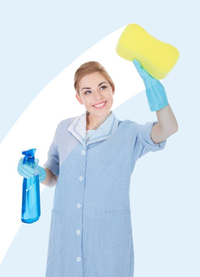 拿着清洁液体和海绵的愉快的佣人 免版税库存图片