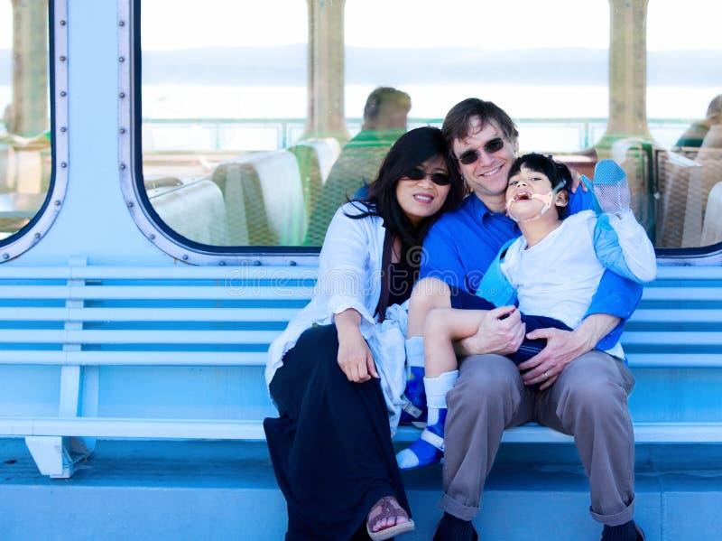 拿着渡轮甲板的人种间夫妇失去能力的儿子 免版税库存照片
