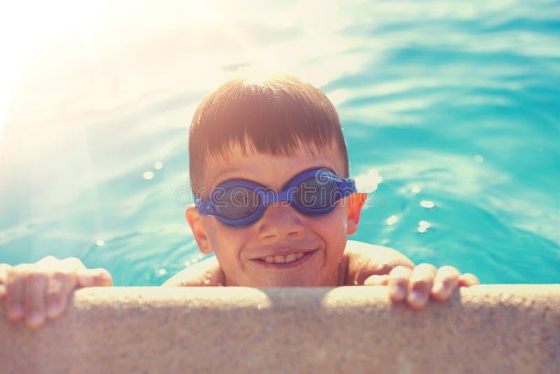 拿着游泳池边缘的风镜的年轻男孩 库存照片