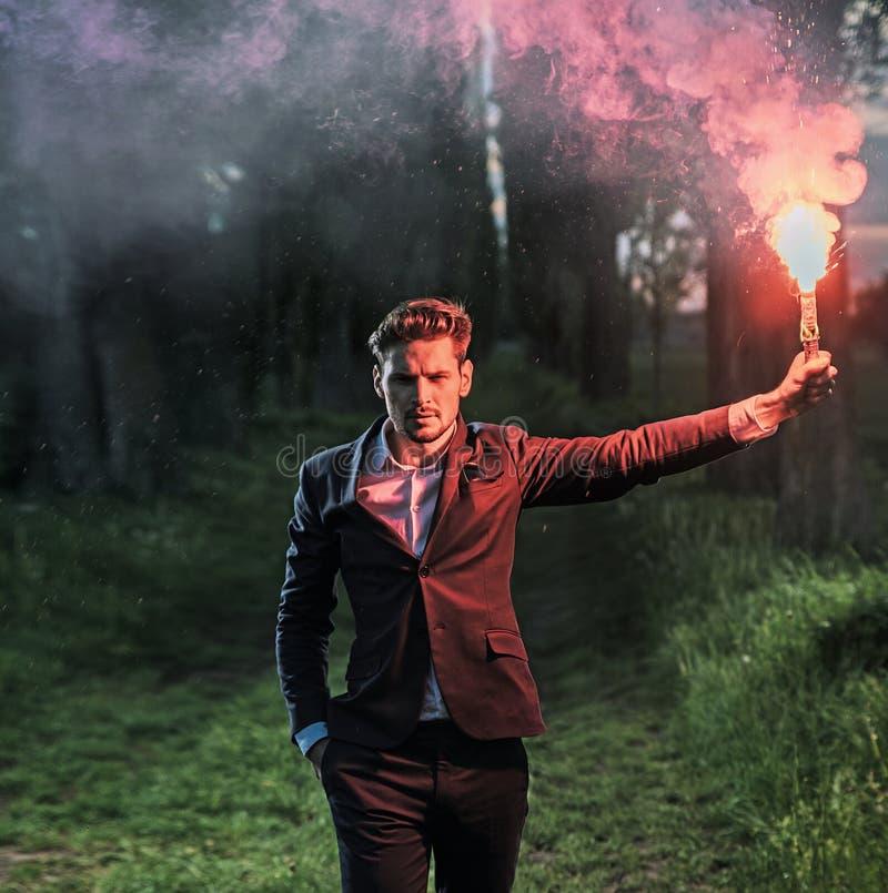 拿着火光的一个雄心勃勃的商人的概念性画象 免版税图库摄影