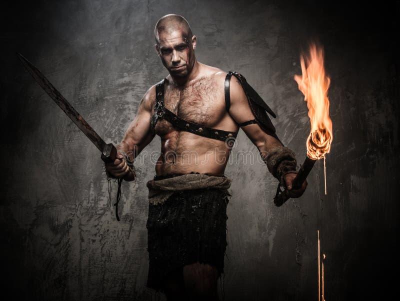 拿着火炬和剑的受伤的争论者 库存照片