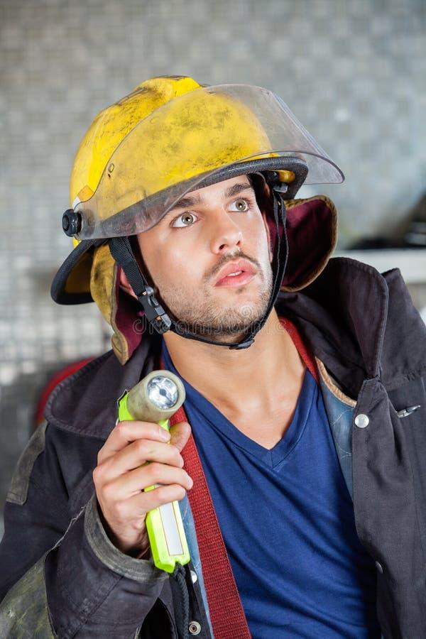 拿着火炬的消防队员在消防局 免版税库存照片