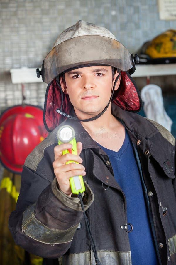拿着火炬的确信的消防队员在火 免版税库存照片