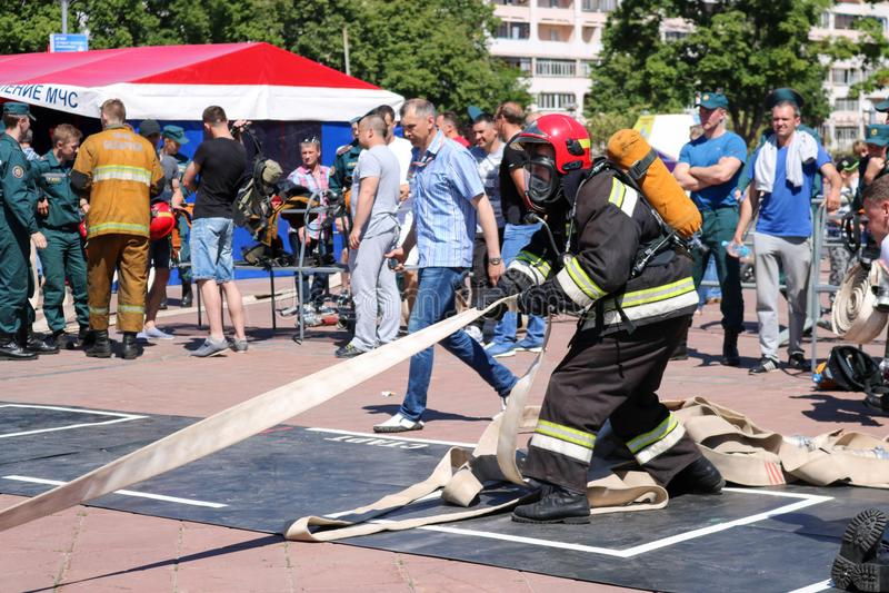 拿着灭火水龙带的一套防火衣服和盔甲的一位消防员在火体育竞赛 米斯克,白俄罗斯, 08 07 2018年 库存图片