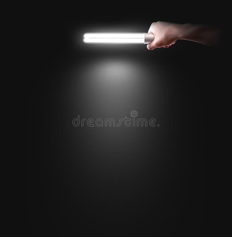 拿着灯的手在墙壁附近, 想法,商标,海报 免版税库存图片