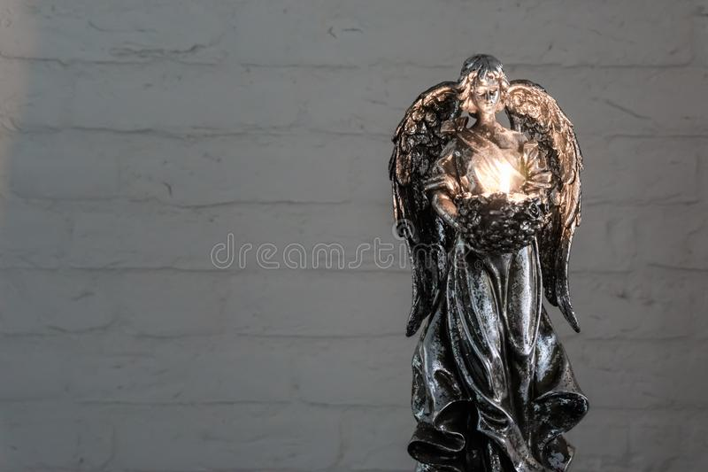 拿着灼烧的茶光蜡烛、传统圣诞节或者精神背景的一个银色天使雕象 免版税库存图片