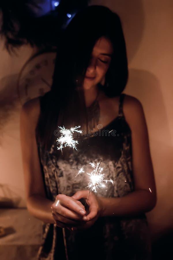 拿着灼烧的闪烁发光物孟加拉光的美丽的时髦的妇女 免版税库存图片