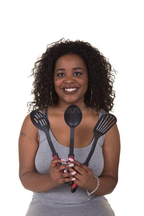 拿着炊事用具的可爱的妇女 图库摄影