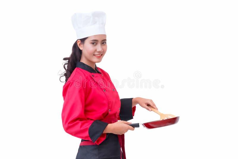 拿着炊事用具的红色制服的厨师妇女 库存照片