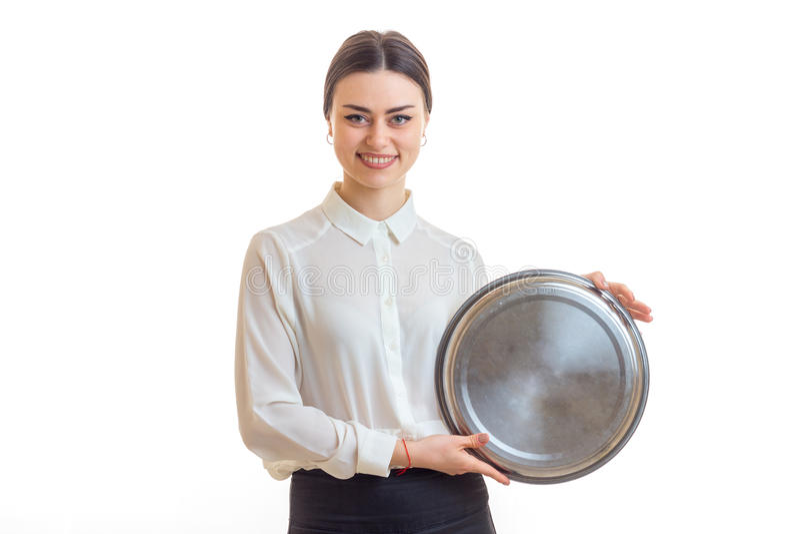 拿着炊具的可爱的年轻女服务员一个大圆的盘子 库存图片