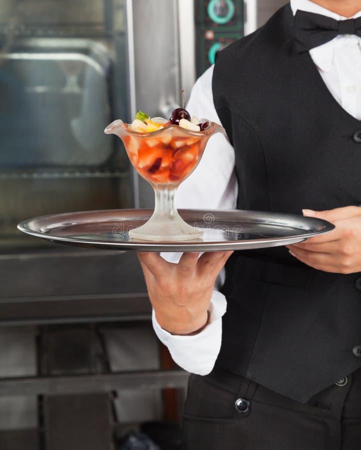 拿着点心盘子的女服务员 免版税库存图片