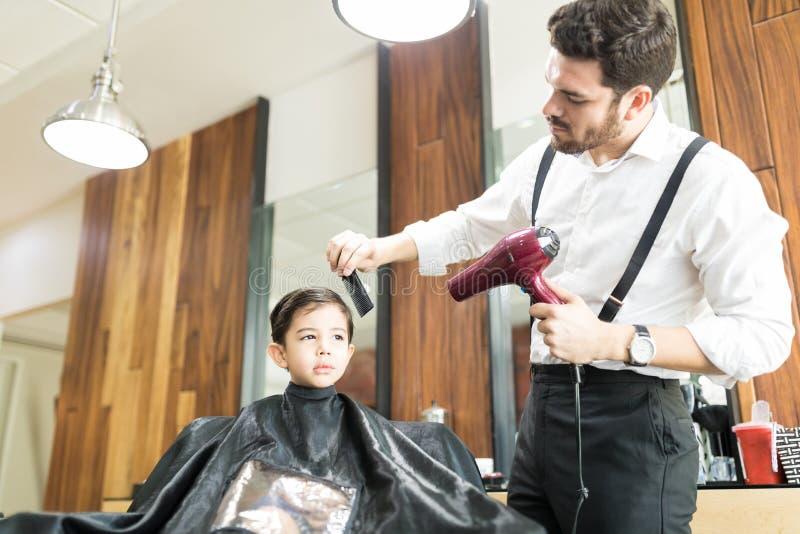 拿着烘干机的美发师,当梳男孩在沙龙时的` s头发 库存图片