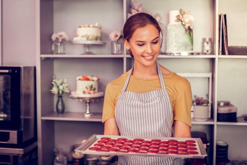 拿着烘烤的盘子的喜悦的深色的女性 库存图片