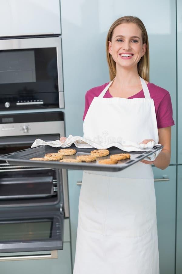 拿着烘烤盘子用曲奇饼的偶然笑的妇女 免版税图库摄影